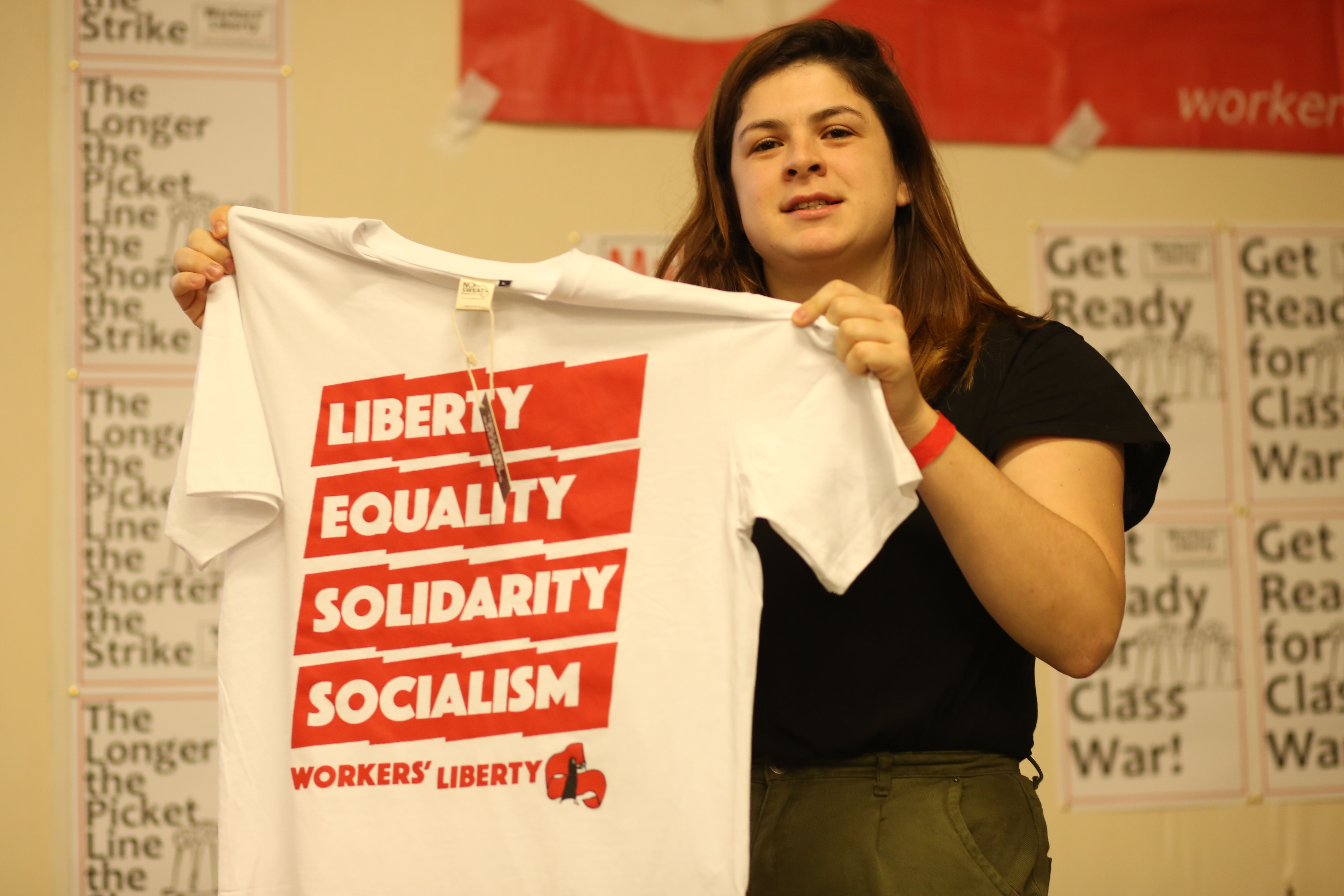 Someone holding up one of the t-shirts, which reads: Liberty, Equality, Solidarity, Socialism, Workers' Liberty.