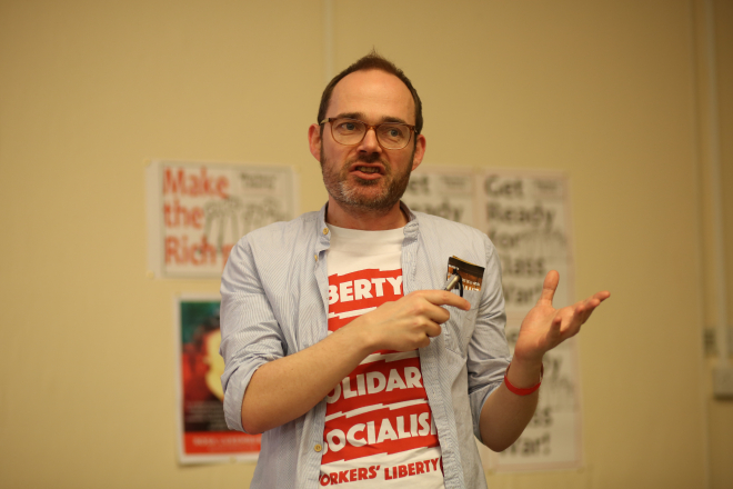 "A sexy communist giving a speech in a t-shirt which reads ""Liberty, Equality, Solidarity, Socialism, Workers' Liberty"""