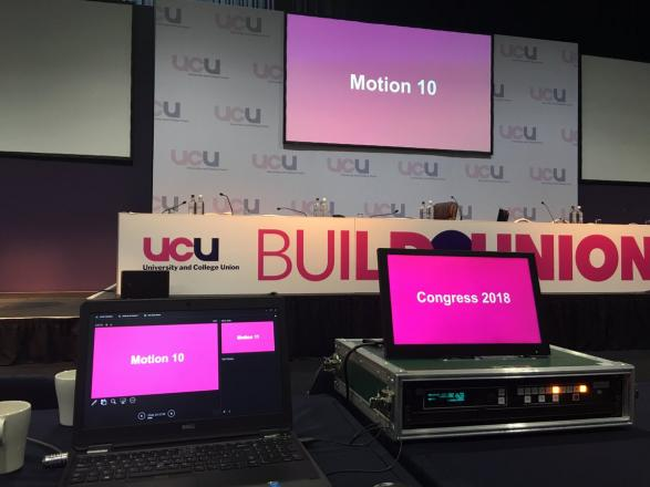 "Image of an empty conference platform with screens showing the text ""motion 10"""