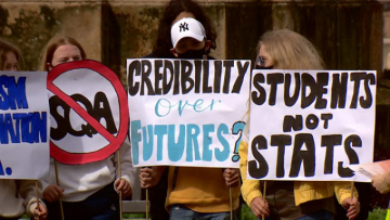 "Scottish pupils holding placards at a protest.  Placards read ""Credibility over futures?"" and ""Students not stats""."