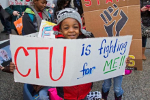 "A child holding a placard that reads ""CTU is fighting for me"""