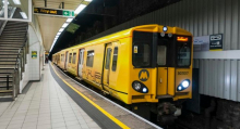 A photograph of a Merseyrail train at a station platform.