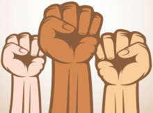 Three raised fists of different skin colours