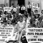 A group of women block an entrance with posters against Thatcher.