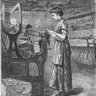 A woman works on an industrial loom.