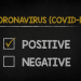"A cartoon of a blackboard with ""Coronavirus (Covid-19)"" written on it, above two boxes marked ""Positive"" and ""Negative"". The ""Positive"" box is checked."