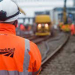 Photograph of a Network Rail worker in orange hi-vis clothing and white hard hat