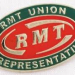 "A photograph of a red and green ""RMT union representative"" badge"